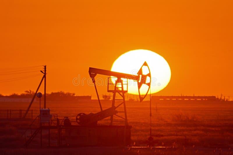Pumpjack på solnedgångbakgrund En Pumpjack är overgrounddrevet för en göra en gentjänst pistongpump i en olje- brunn royaltyfria bilder