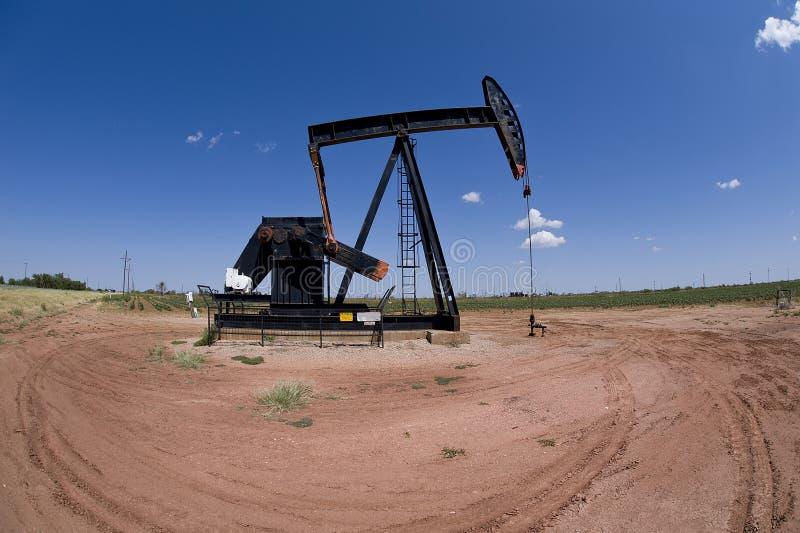 Pumpjack sobre o poço de petróleo imagem de stock