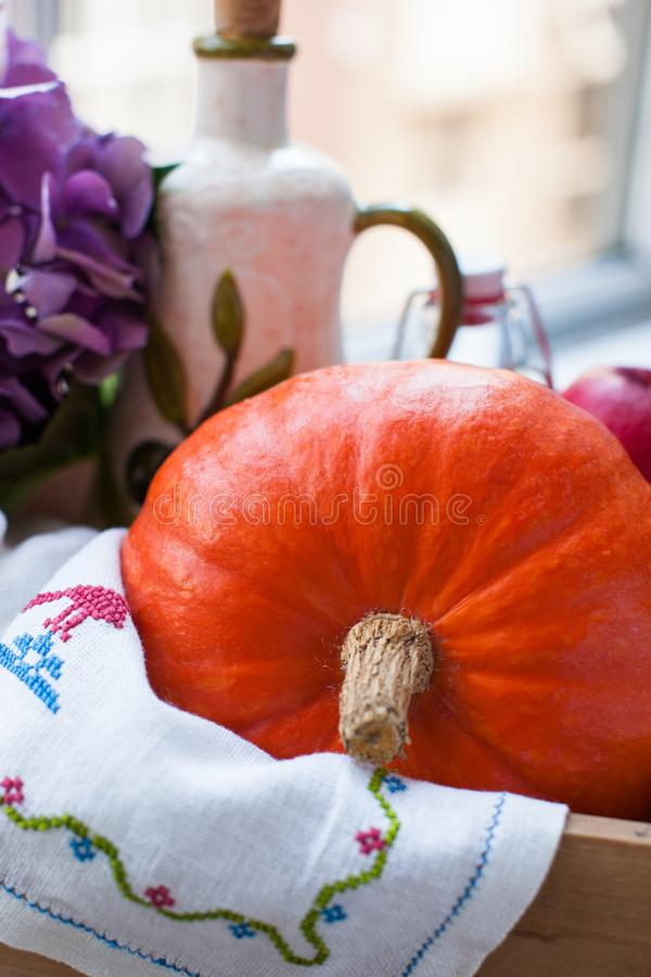 Pumpkin, apples and flowers in a wooden box near the window. Home coziness and comfort. Products for health and beauty. Pumpkin, apples and flowers in a wooden royalty free stock photo