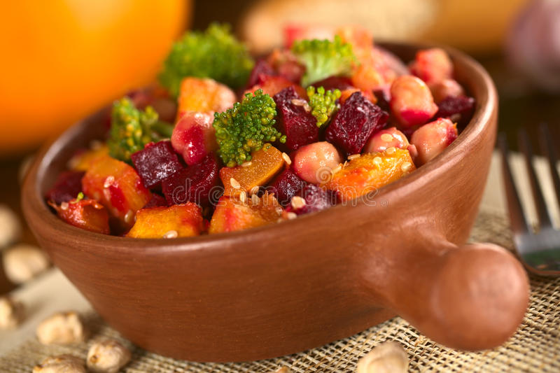 Pumpkin, beetroot, broccoli and chickpea salad. Garnished with sesame seeds (Selective Focus, Focus on the bigger broccoli floret in the front and the royalty free stock image