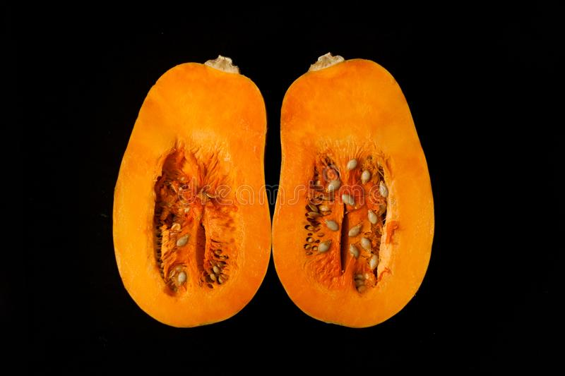 Pumpkin on a black background. Creative minimalism, food photography. Two halves of a pumpkin with seeds on a black background. Creative minimalism, dark and royalty free stock photo
