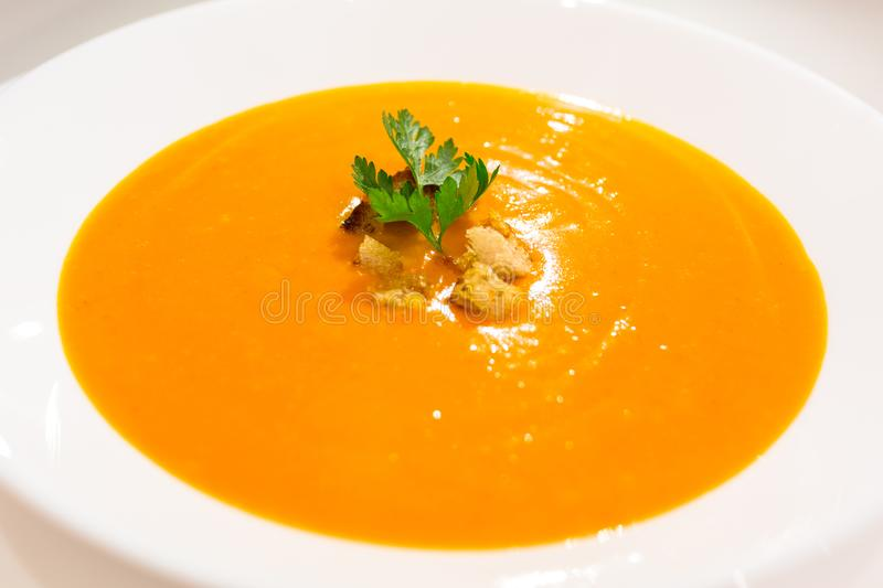 Pumpkin and carrot soup in a bowl stock image