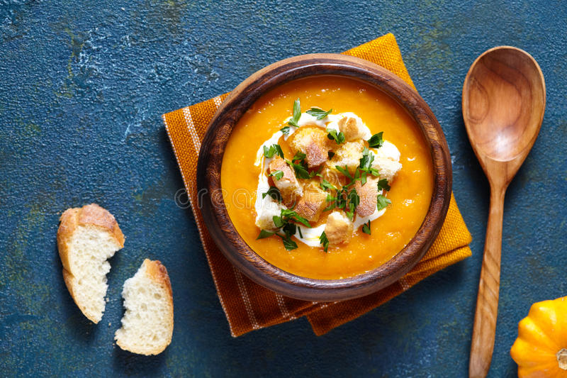 Pumpkin and carrot soup with cream, croutons on creative blue background. Top view. For Thanksgiving, halloween. stock image