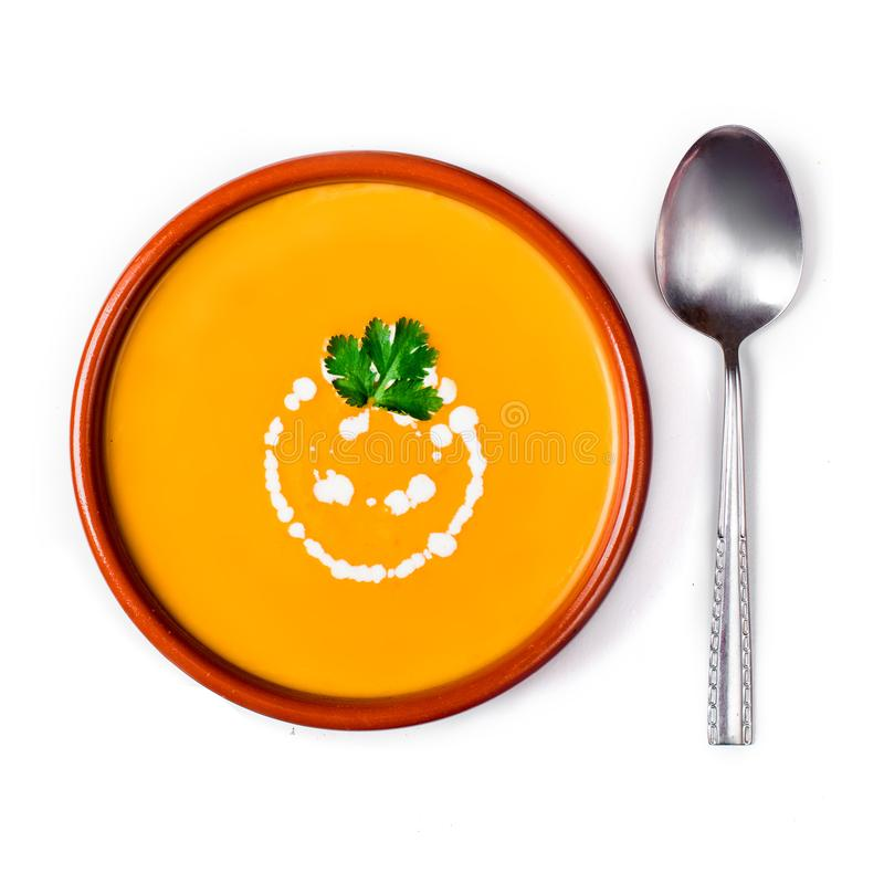 Pumpkin and carrot soup with cream and herbs isolated on white stock photo