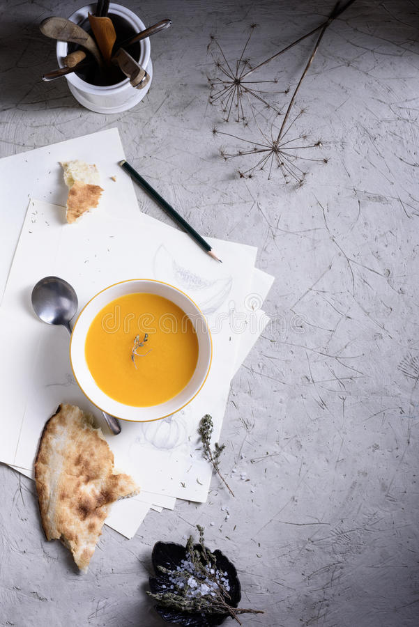 Pumpkin and carrot soup with cream and herbs on a table. stock photography