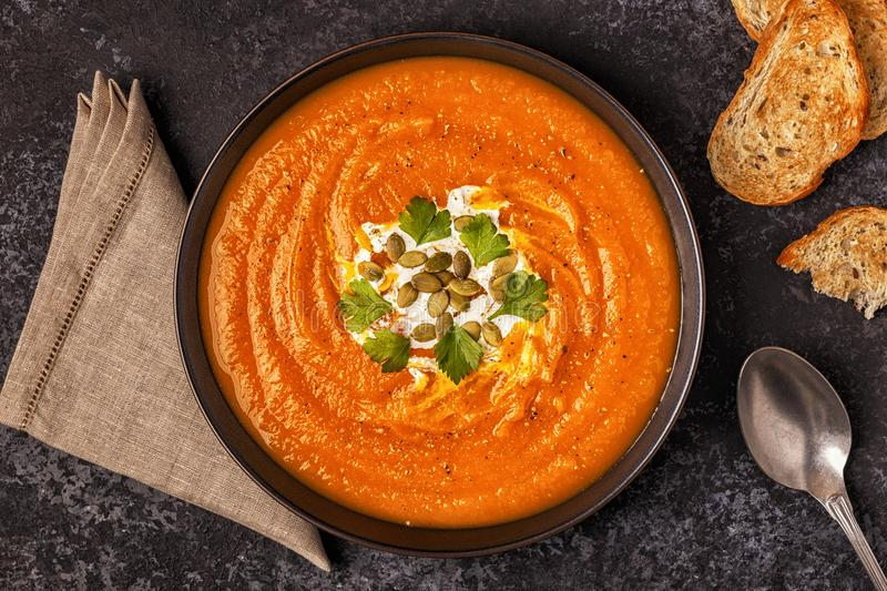 Pumpkin and carrot soup with cream, seeds and parsley. stock photography