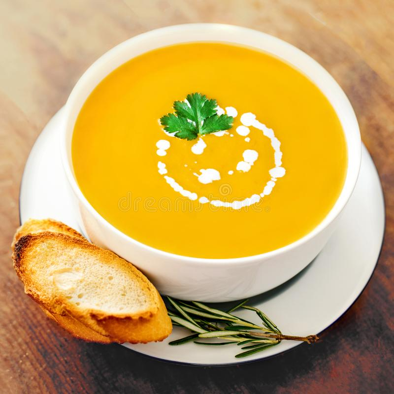 Pumpkin and carrot soup in a white bowl on rustic wooden table. stock photography
