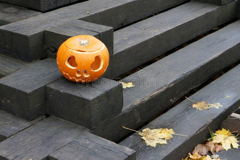 Pumpkin with carved eyes and mouth on a black wooden staircase. stock photos