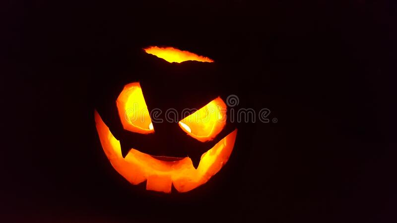 Pumpkin carved with scary face to scare on halloween, with candle inside and black background.  stock image