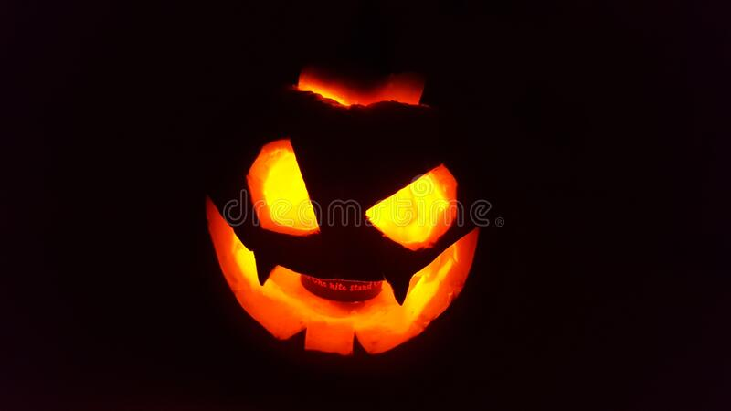Pumpkin carved with scary face to scare on halloween, with candle inside and black background.  royalty free stock images