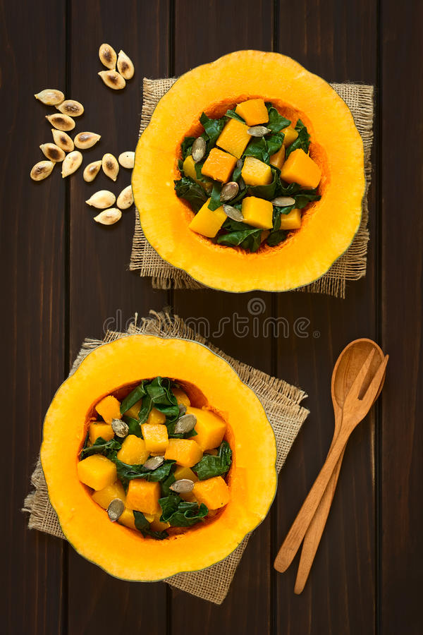 Pumpkin and Chard Salad. With roasted pumpkin seeds served in pumpkin halves, photographed overhead on dark wood with natural light royalty free stock photos