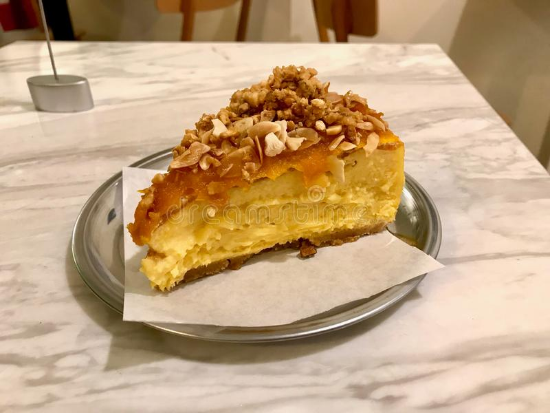 Pumpkin Cheesecake Slice with Crispy Nuts and Almonds served at Coffee Shop with Silver Plate / Cafe Shop royalty free stock images