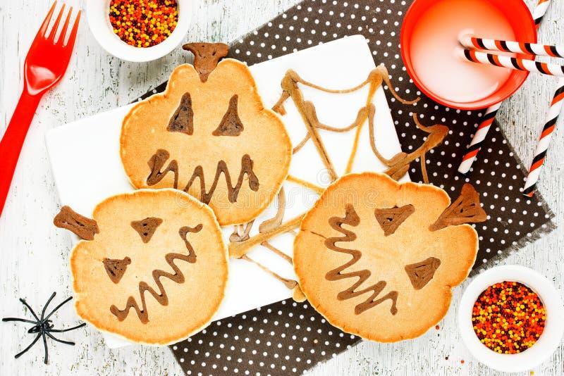 Pumpkin chocolate pancakes shaped Jack-o-lanterns for Halloween royalty free stock photo
