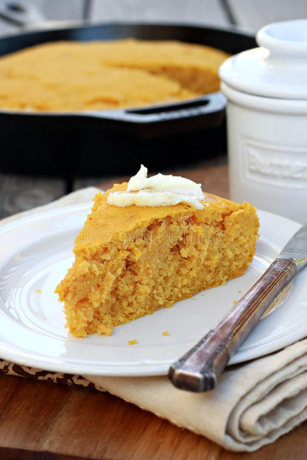 Pumpkin Cornbread. Slice of pumpkin cornbread with butter royalty free stock photos