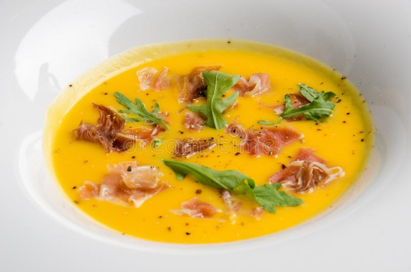 Pumpkin cream soup with bacon and arugula in a white plate on a dark wooden background among vegetables. Close-up. Space stock photography
