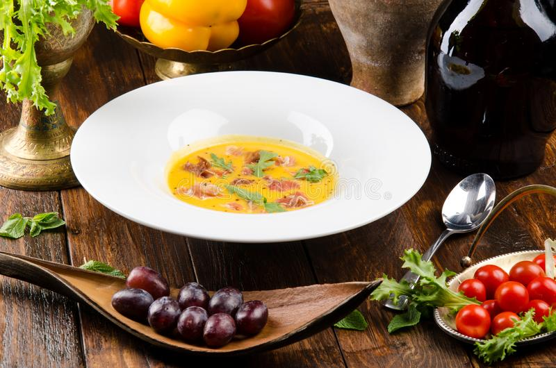 Pumpkin cream soup with bacon and arugula in a white plate on a dark wooden background among vegetables. Close-up. Space stock photos