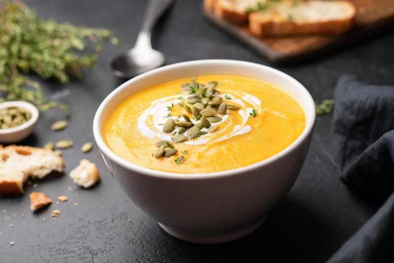 Pumpkin cream soup in bowl on black concrete background stock images