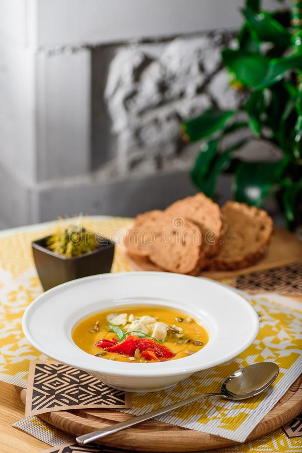 Pumpkin cream soup with cheese Dor Blue, bell pepper, pumpkin seeds in a white plate on yellow set on a wooden table royalty free stock photography