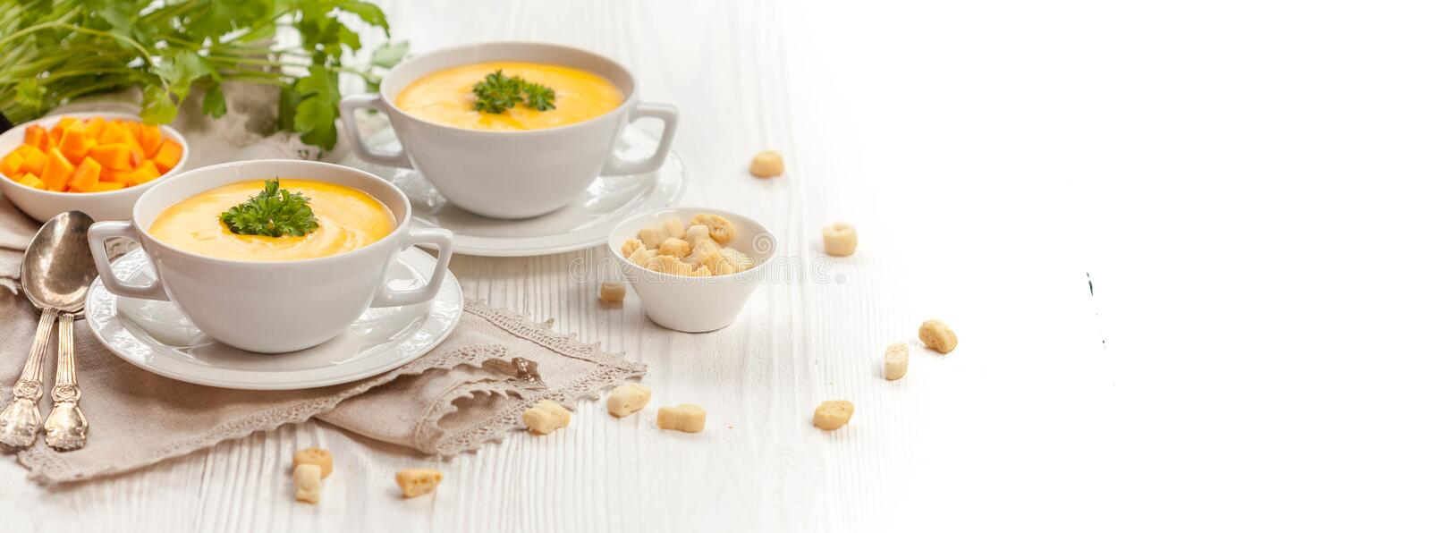 Pumpkin cream soup. With croutons, raw fresh pumpkin pieces and herbs on a white rustic wooden background, Autumn concept. Long web format, banner royalty free stock photography