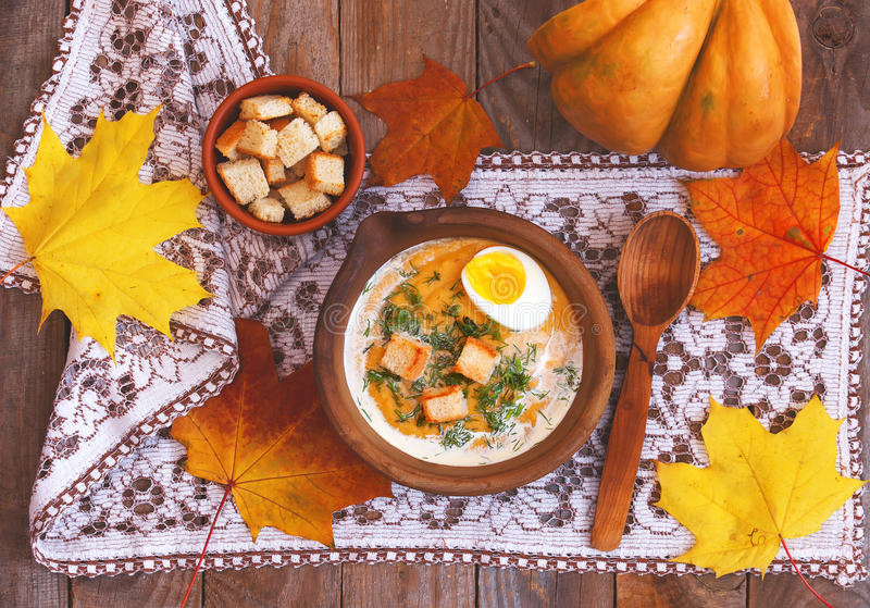 Pumpkin cream-soup decorated with maple leaves, boiled egg and c royalty free stock photos