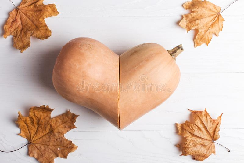 Pumpkin cut in the shape of a heart and yellow leaves, autumn and crop concept royalty free stock photography