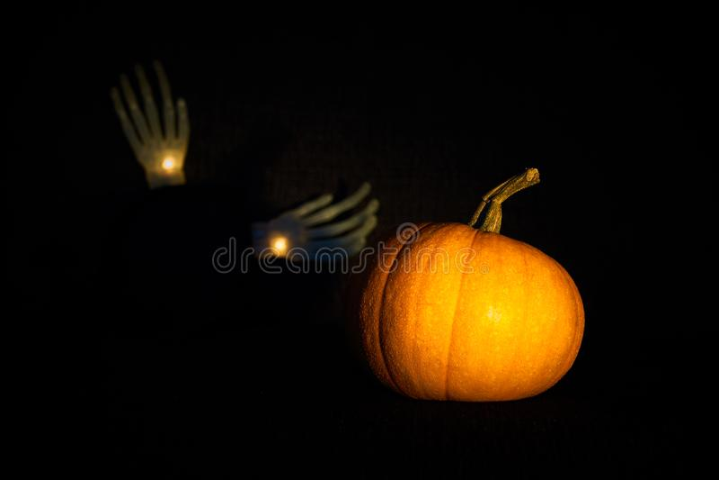 Pumpkin in darkness with blurred skeleton hands. Halloween mood. stock photography