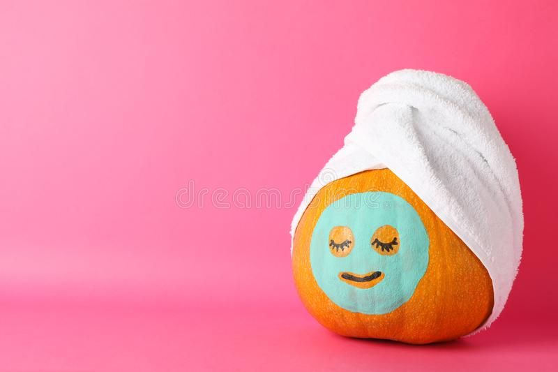Pumpkin with facial mask and towel on pink background royalty free stock image