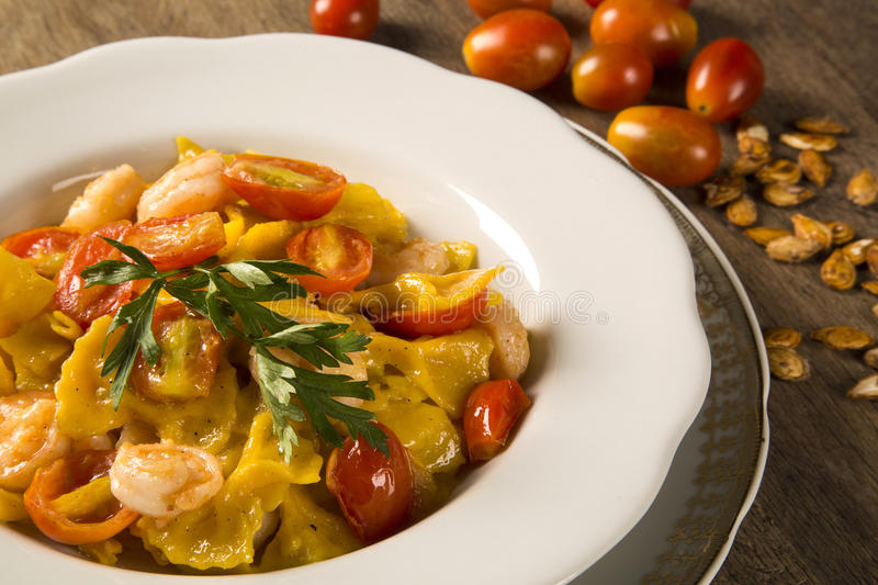 Pumpkin farfalle with shrimp and cherry tomato royalty free stock image