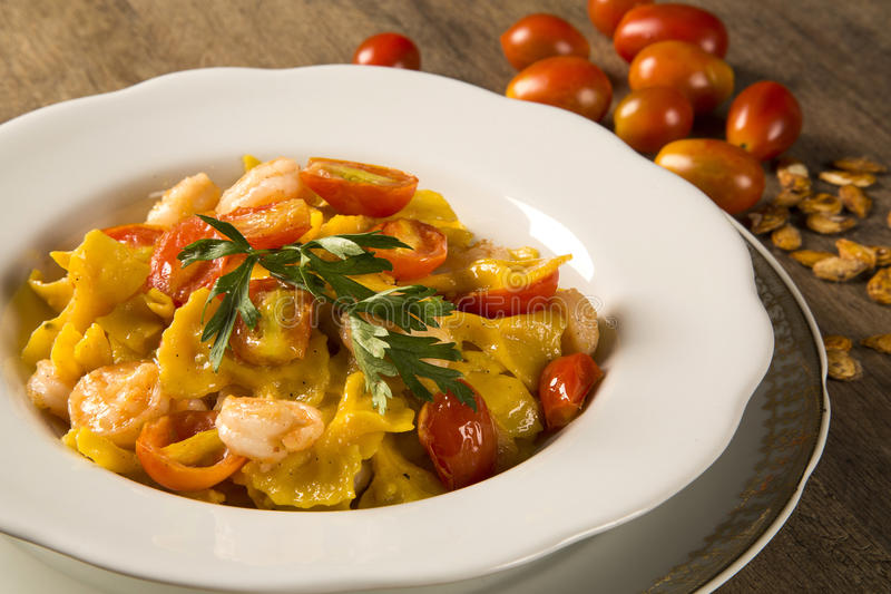 Pumpkin farfalle with shrimp and cherry tomato stock image
