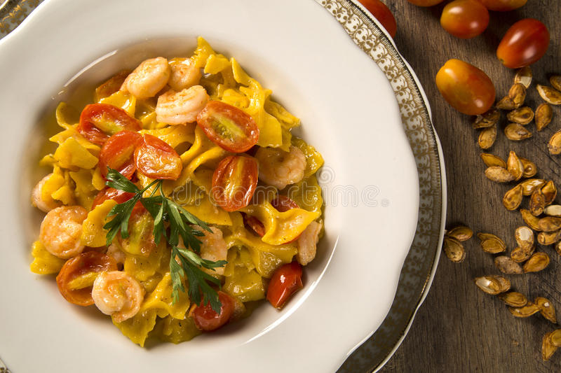 Pumpkin farfalle with shrimp and cherry tomato royalty free stock images