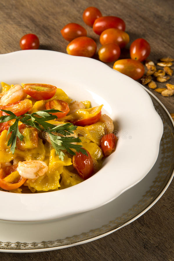 Pumpkin farfalle with shrimp and cherry tomato stock photography