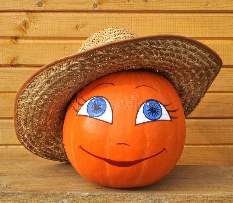 Pumpkin with female face in straw hat. Pumpkin with female face in a straw hat against wooden boards, photo by a Halloween stock photo
