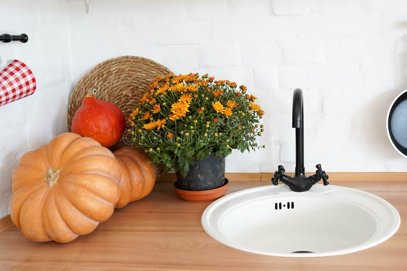 Pumpkin, flowers and sink on wooden table, scandinavian autumn interior stock images