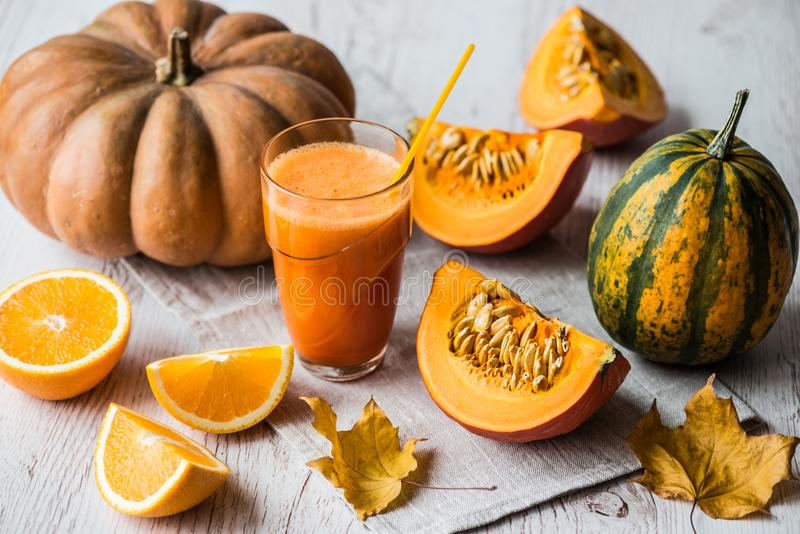 Pumpkin fresh juice with ingredients on white wooden background. detox healthy drink royalty free stock images