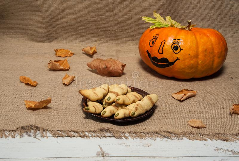 Pumpkin with a funny painted face, homemade cookies `witch`s finger`, autumn leaves on a textile background. stock photos