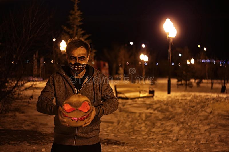 Pumpkin for Halloween in hands scary face stock image