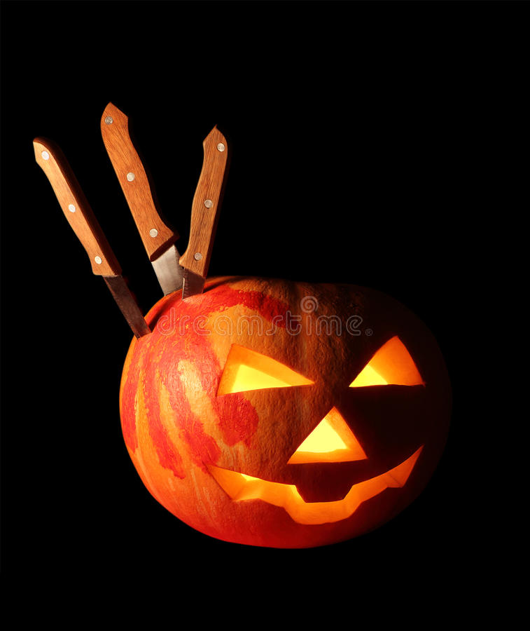 Pumpkin for Halloween isolated over black. Pumpkin for Halloween with a track of blood-stained palm and several knives isolated over black royalty free stock image