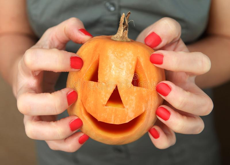 Pumpkin in hands for Halloween. Small yellow pumpkin in hands during the celebration Halloween royalty free stock photos