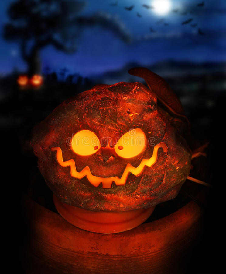 Pumpkin head. Spooky Halloween image of a glowing jackolantern with eerie night sky in background including moon and bats stock photo