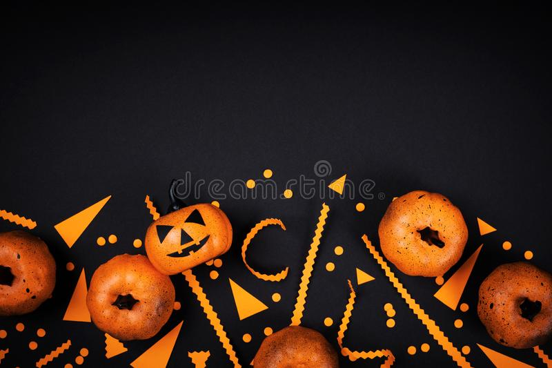 Pumpkin heads and confetti for Halloween party decor on black table top view. Flat lay style. Pumpkin heads and confetti for Halloween party decor on black stock photography