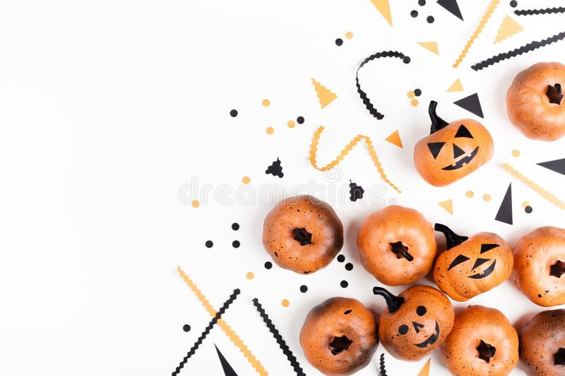Pumpkin heads and confetti for Halloween party decor on white background top view. Flat lay style. Pumpkin heads and confetti for Halloween party decor on white stock photo