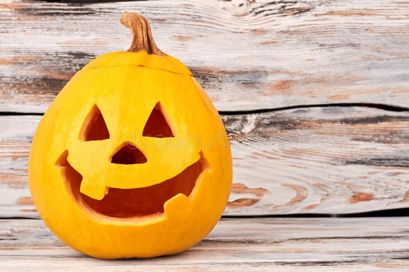 Pumpkin Jack-O-Lantern with happy face. Funny smiling Halloween pumpkin on wooden background. Halloween greeting card stock photo