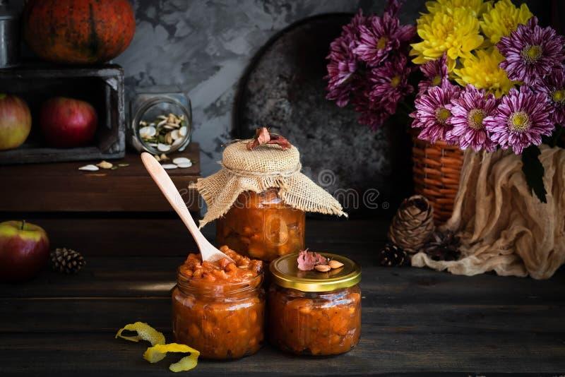 Pumpkin, lemon and apricot kernel jam. Pumpkin jam on a dark rustic background. Autumn harvest. Cozy autumn still life. Homemade preparations for the winter royalty free stock photo