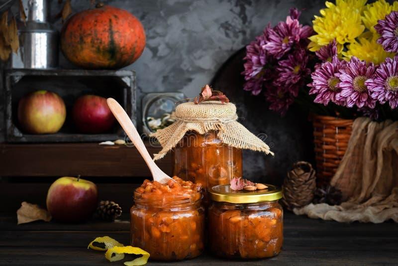 Pumpkin, lemon and apricot kernel jam. Pumpkin jam on a dark rustic background. Autumn harvest. Cozy autumn still life. Homemade preparations for the winter stock photos