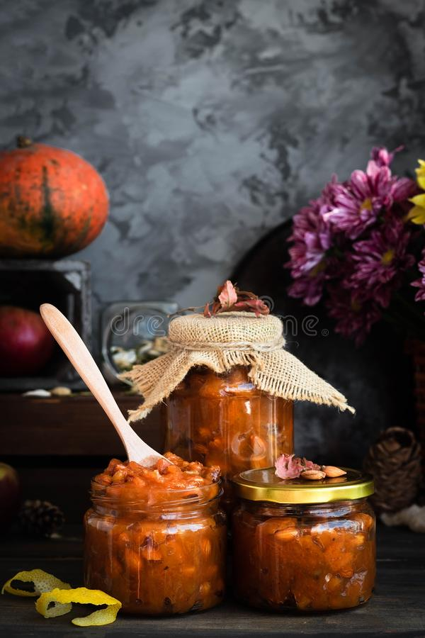 Pumpkin, lemon and apricot kernel jam. Pumpkin jam on a dark rustic background. Autumn harvest. Cozy autumn still life. Homemade preparations for the winter royalty free stock images