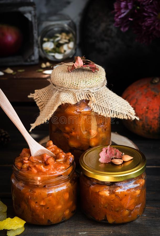 Pumpkin, lemon and apricot kernel jam. Pumpkin jam on a dark rustic background. Autumn harvest. Cozy autumn still life. Homemade preparations for the winter stock photo
