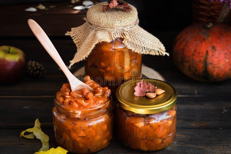 Pumpkin, lemon and apricot kernel jam. Pumpkin jam on a dark rustic background. Autumn harvest. Cozy autumn still life. Homemade preparations for the winter stock image