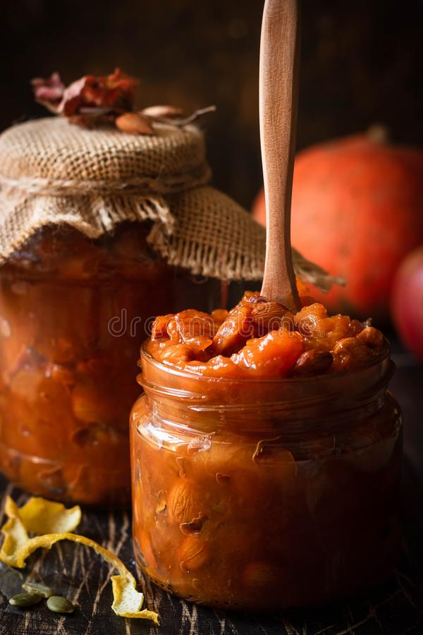 Pumpkin, lemon and apricot kernel jam. Pumpkin jam on a dark rustic background. Autumn harvest. Cozy autumn still life. Homemade preparations for the winter royalty free stock photography