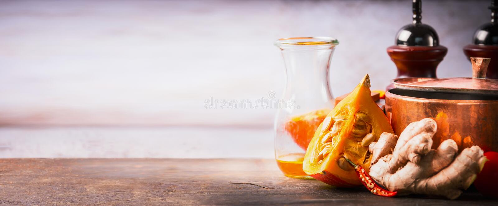 Pumpkin on kitchen desk table with cooking pot, oil and ginger, front view. Food background for Autumn cooking inspiration. And Recipes, banner stock images
