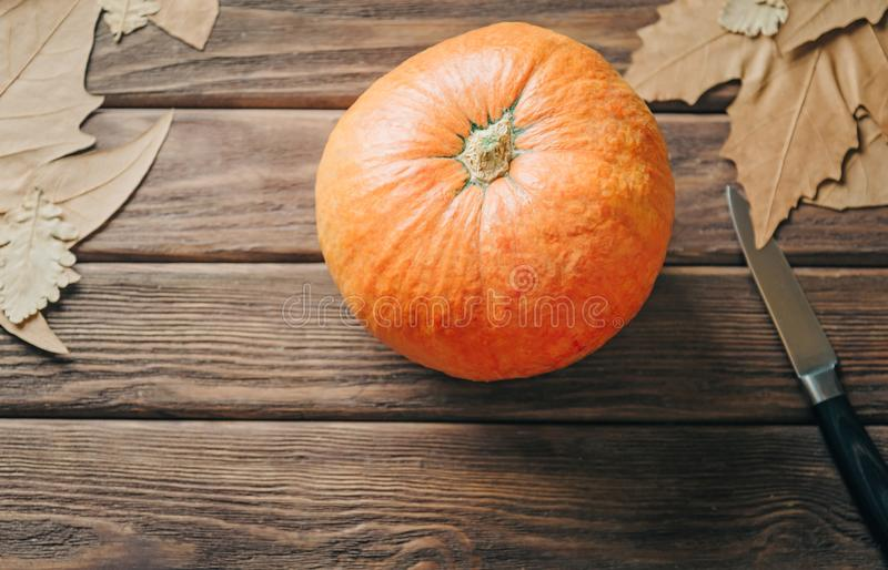 Pumpkin and knife on wooden table, preparation to Halloween. stock photo